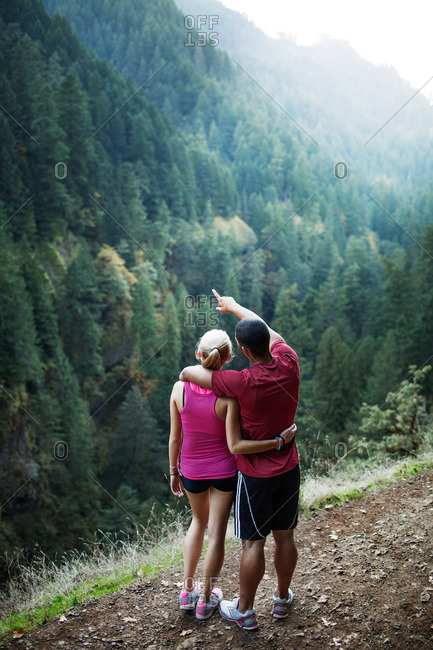 Young couple looking at view from a mountain trail