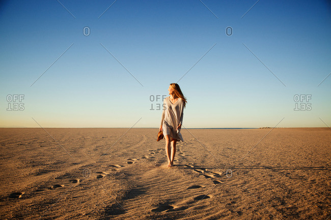 Young woman walking on the beach at sunset