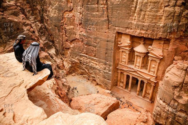 Petra, Jordan - November, 2010: Bedouins sitting on a cliff looking down to the Treasury (El Khazneh) in Petra, Jordan