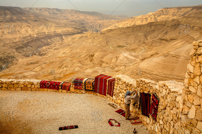 Man selling rugs above Wadi Mujib escarpment at a lookout along Kings Highway in Jordan