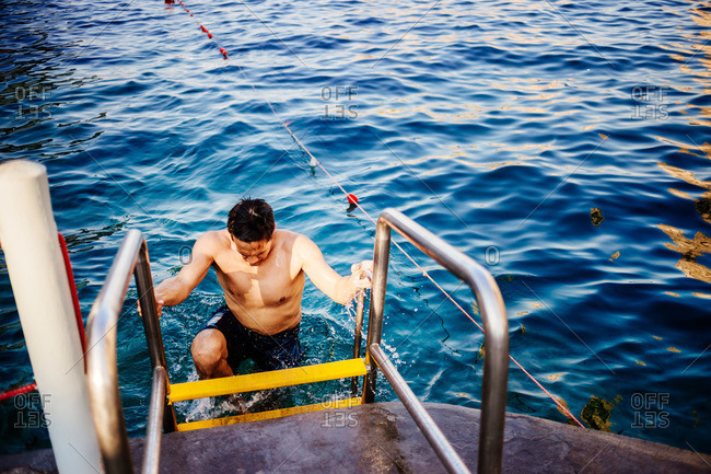 Man climbing a ladder in the sea in Capri, Italy