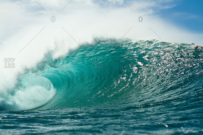 Tall blue wave crashing over