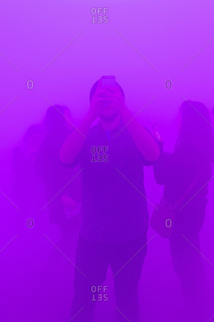 People taking photos in a purple fog
