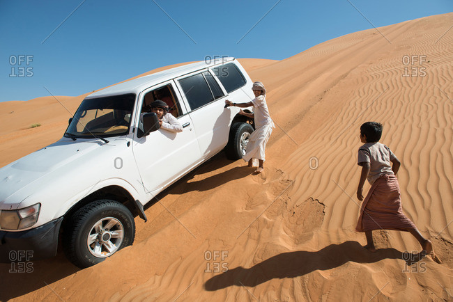 Wahiba Sands desert, Oman - February 3, 2015: Omani children playing in desert sand dunes with vehicle