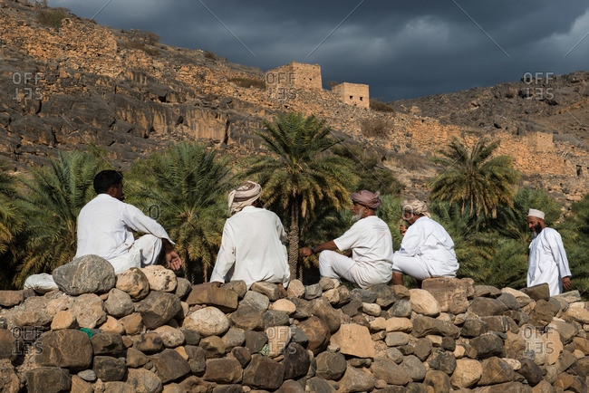 Hajar Mountains, Oman - February 5, 2015: Omani farmers gather in a field and greet each other, Hajar Mountains