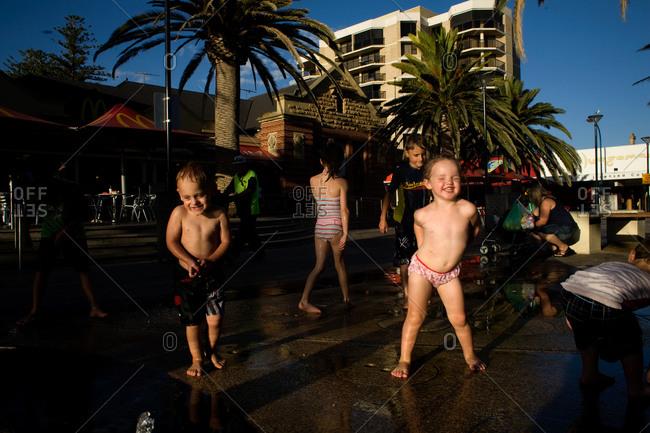 Glenelg, Australia - January 30, 2009: People cool off in the water sprinklers on the promenade of beach