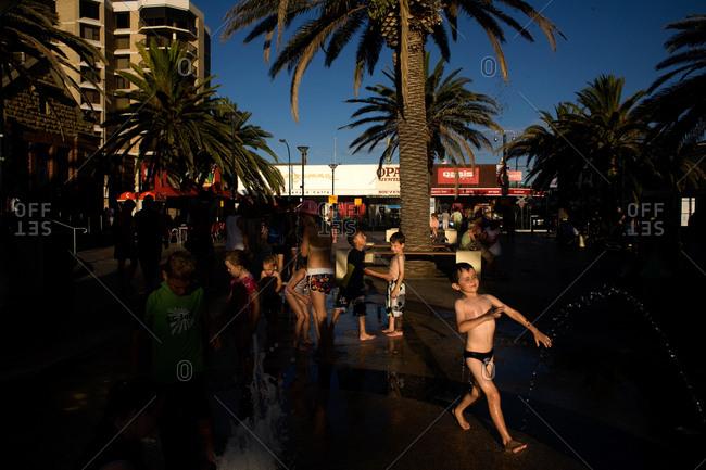 Glenelg, Australia - January 30, 2009: People cool off in the sprinklers on the promenade of Glenelg beach