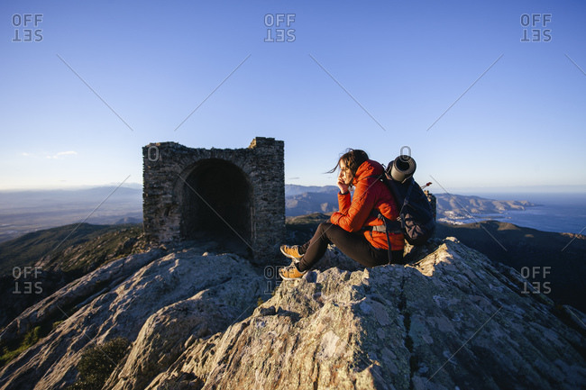 Female hiker resting on mountaintop looking at view