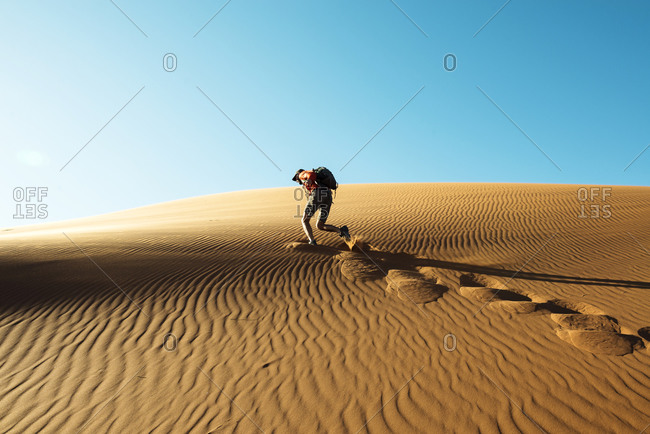 Man climbing a dune at sunset in Namib Desert, Namibia