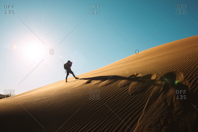 Man taking pictures on a dune at sunset in Namib Desert, Namibia