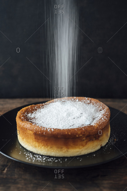 Sprinkling Japanese cheese cake with icing sugar