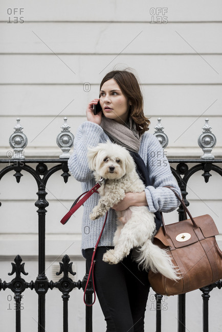 Young woman holding her dog while talking on her phone