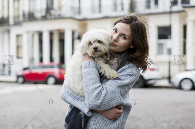 Portrait of young woman holding her dog on her arms