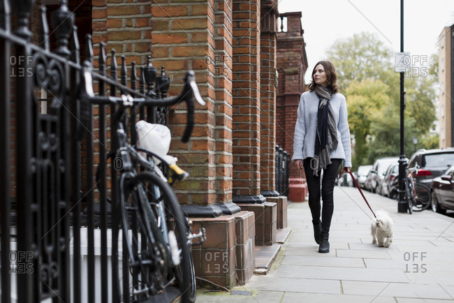 Young woman walking with her dog in London