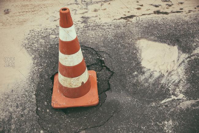 Traffic cone on broken tarmac after heavy rainfalls