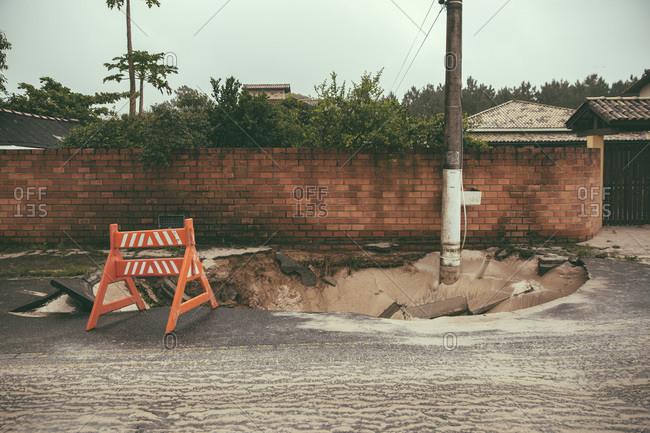 Traffic barrier on broken tarmac after heavy rainfalls