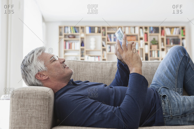 Mature man lying on the couch at home using digital tablet