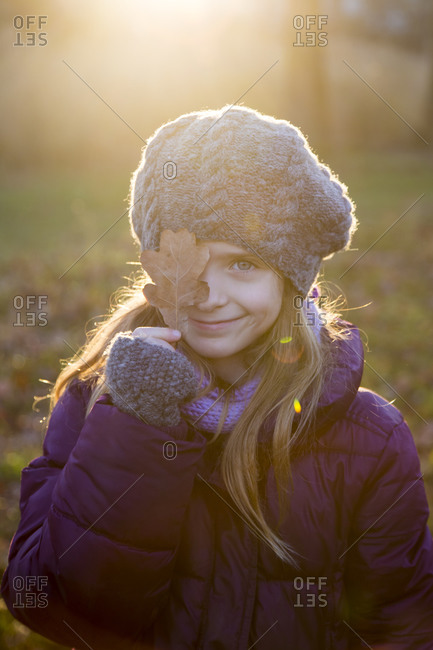 Portrait of smiling girl at evening twilight covering one eye with an autumn leaf
