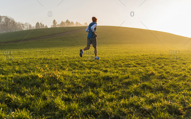Young man jogging at sunrise