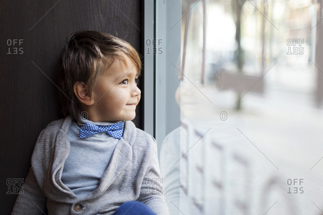 Portrait of smiling little boy with bow tie looking through window display