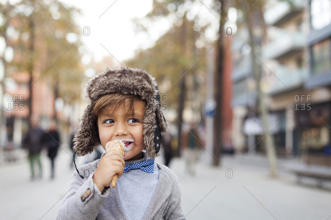 Portrait of happy little boy with ice cream cone on the street