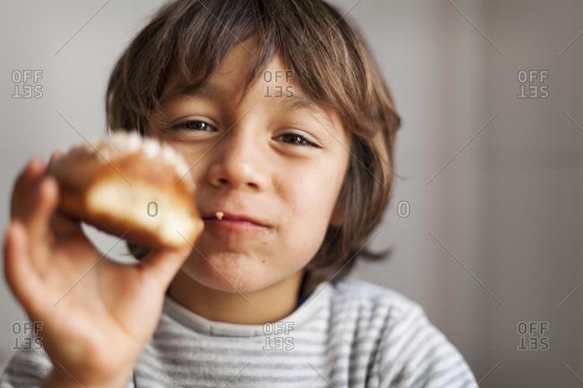 Little boy holding brioche