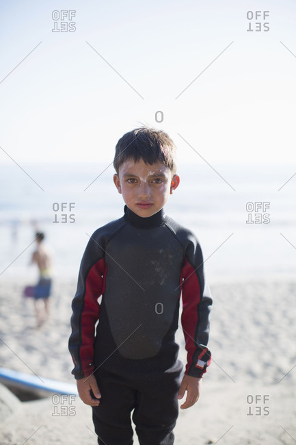 A little boy stands alone, there is an uneven coats of powder on his face and full sleeve t-shirt