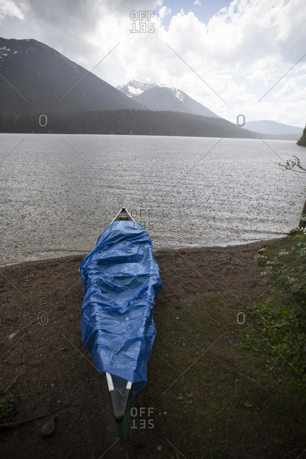 A canoe is covered by a blue tarp during a heavy rain storm