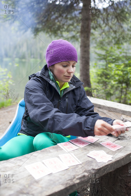A woman deals cards  on a wooden table while camping