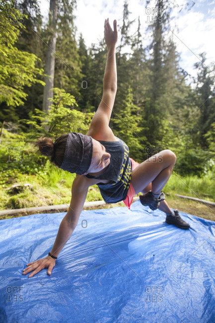 A woman completes a morning fitness routine on a blue tarp while camping