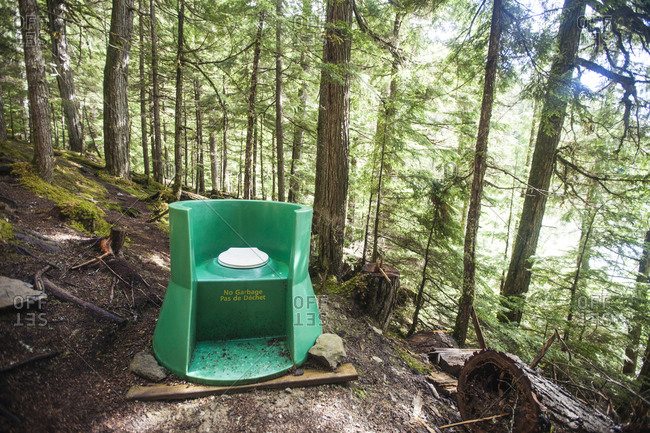 An open air outhouse located in the forest near a campsite