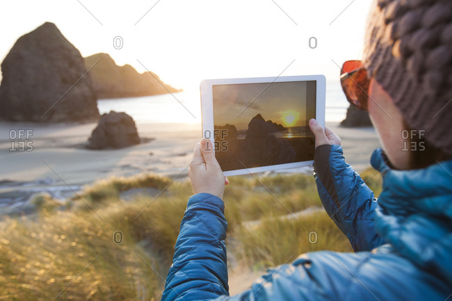 Close up of a woman taking a picture with a tablet at dusk on Gold Beach