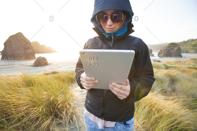 Woman with tablet on Gold Beach