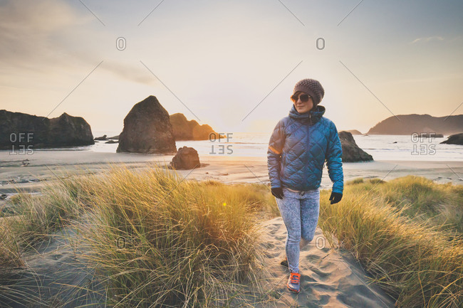 Woman walking on Gold Beach at sunset