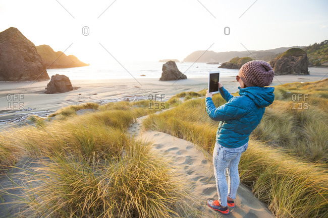 Woman using a tablet taking a picture of the sunset on Gold Beach