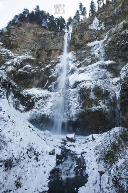 Icy water cascades over Multnomah Falls during winter in the Columbia River Gorge