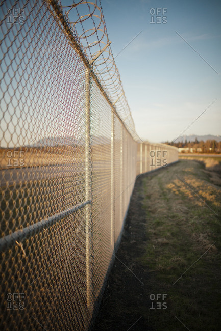 Chain-linked fence with a barbed wire finish