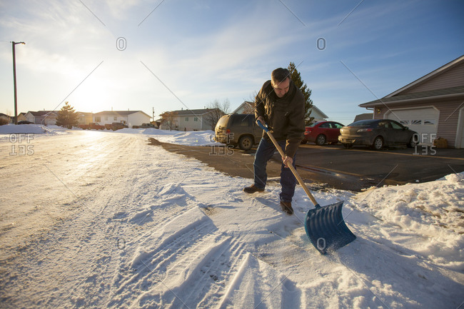 A man scrapes snow off his driveway in northern Alberta