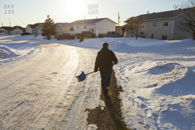 An man walks a suburban street with a snow shovel in his hand