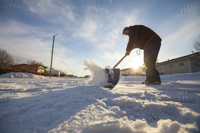 A man shovels snow off his driveway in northern Alberta in the evening