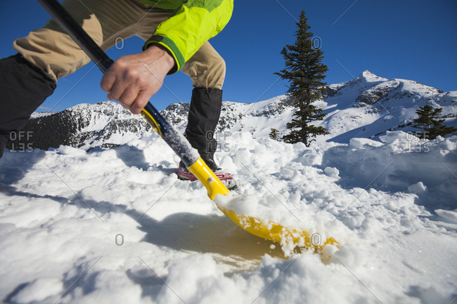 A climber shovels snow in order to make a flat spot to pitch his tent
