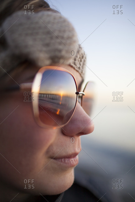 Portrait of a young woman wearing sunglasses at sunset, BC, Canada