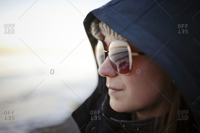 Portrait of a young woman wearing sunglasses and a hooded jacket