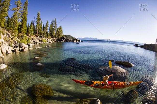 Woman kayaking in Secret Harbor, Tahoe, CA