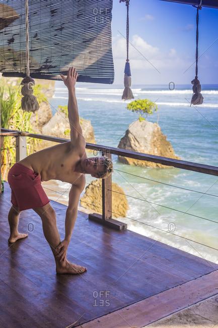 Man twisting during morning yoga near ocean