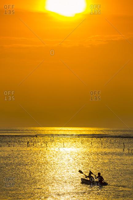 Kayaking at sunset time - Offset
