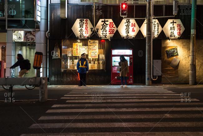 Osaka, Japan - December 29, 2015: Pedestrian and traffic officer at a crosswalk at night