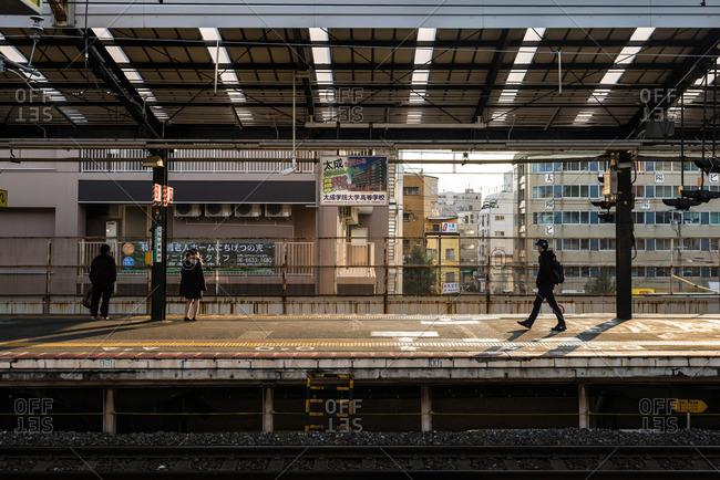 Osaka, Japan - December 31, 2015: Commuters waiting for trains at Shin-Imamiya Station