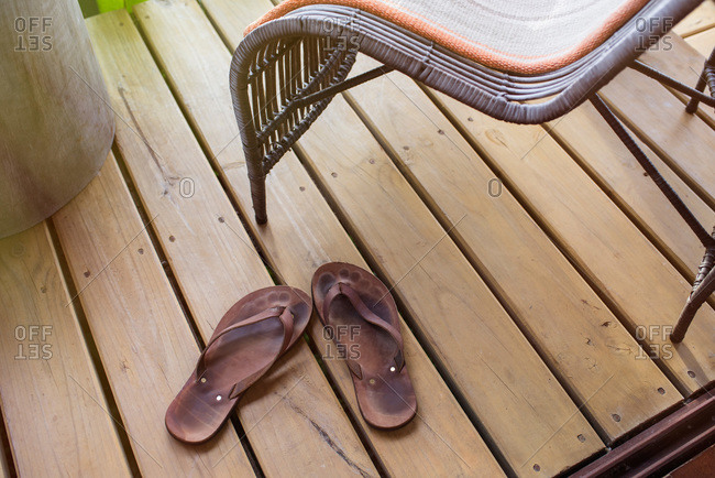 Leather flip flops on a wooden deck