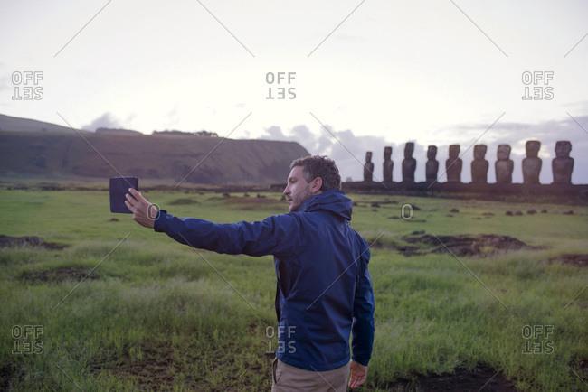 Man taking a selfie near maoi statues on Easter Island